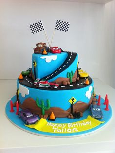 Cars 2 Birthday Cake 2 tier chocolate mud covered in ganache and fondant. not arty enough to be able to mould vehicles unfortunatley so...