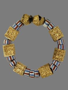 Africa | Asante people, Ghana - 19th - early 20th century. Bracelet / amulet (suman) composed of 8 lost wax cast gold beads which alternate with fourteen glass beads decorated with red, white and blue horizontal stripes.
