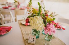 Mason jar centerpieces with bright flowers and burlap table runner | Photo: Tina Bass Photography