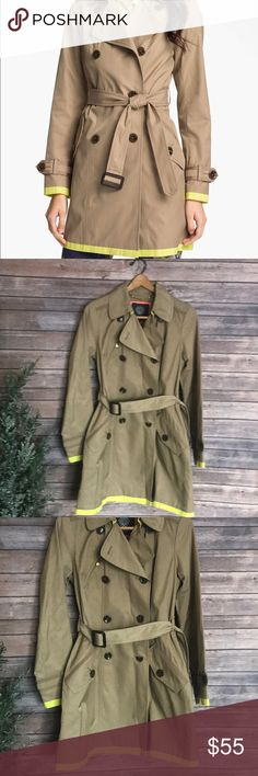 """Vince Camuto Joanna Tan neon trench coat NWOT Vince Camuto Joanna Tan neon trench coat NWOT. Sleek and more gorgeous in person. Color is a dark tan, dark khaki color.  The iconic khaki trench gets a modern twist from pops of a citrus hue around the hem and cuffs. For more subtle trim, tonal ribbon edges the cuff belts, pockets and back of double-breasted.  Approx. length from shoulder: 35"""". Zip chest pocket; button-flap front pockets. Removable belt. Inverted back pleat. Fully lined…"""
