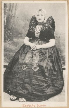 Vrouw in Axelse streekdracht. De vrouw draagt over de ondermuts en het oorijzer een 'trekmuts'. Ze draagt 'dubbele strikken' (dubbele, klaverbladvormige gouden oorijzerhangers) aan de 'krullen' (oorijzeruiteinden) van het oorijzer. Op de schoenen worden zilveren gespen gedragen. na 1905 #Axel