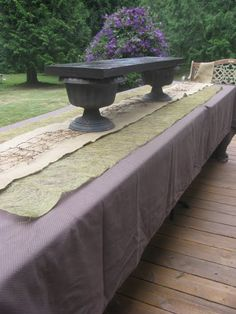 Plastic urns painted black add height for reception table. Layering of dark brown burlap, green , tan and burlap ribbon...