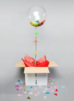 Confetti / tissue stuffed balloon in a box: How do you stuff a deco bubble 20 with tissue shapes / confetti without bending or creasing the tissue? Is there a stuffing machine for this purpose, or