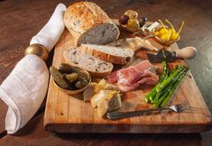 Cutting Board with Antipasto of meat, cheese, pickles, asparagus and artichoke hearts with whole grain bread Sacramento Food, Ambrosia Recipe, Plate Presentation, Antipasto Platter, Restaurant Marketing, Artichoke Hearts, Whole Grain Bread, Menu Design, Food Styling