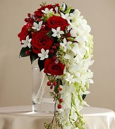 The FTD® Here Comes the Bride™ Bouquet makes a dramatic presentation perfect for the bride that likes to hold everyone's attention. White dendrobium orchids cascade from a compact bouquet of red roses