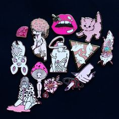 Black and pink . . . [Image description: 12 enamel pins arranged on black paper. The pins are a puking girl by @culturalvoid and @oasis_of_hate  a bat by @juicette  a gem by @lizharrydesign  a flower faced woman by @yaspaints  a mushroom girl by @gildedcreaturesart  a sci fi babe by @culturalvoid a flower by @britsketch  a mouth by @itsthesassygirl  a kitten by @darlingdistraction  a rabbit triangle by @dorrarium  a hand and cigar cutter by @highfivepins  and a dissected rat by @littlewounds…