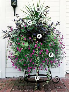 An elevated ironwork container stands partially hidden behind the lush blooms of a skirt of petunias. A layer of foliage plants rises above, which creates even more interest.