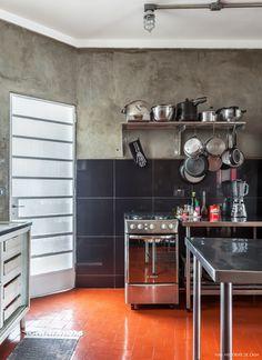 O estilo industrial nessa cozinha é bem marcado pelos móveis de aço e parede de cimento queimado.