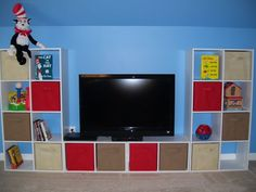 DIY Storage Unit for kids room or playroom, or maybe an entertainment center idea! (2) 8 cube ClosetMaid Cubes on outside and (2) 2 cubes glued together in middle to create a bench, all adhered to wall! Fabric pull out bins also from Target!