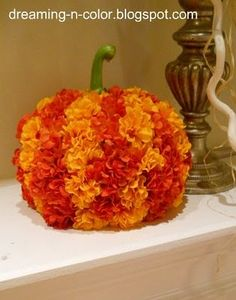 Hot  glue flowers to cheap dollar store pumpkin and add pretty stem.
