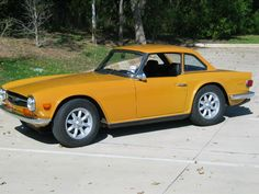 Triumph TR6. Want one. And I didn't know you could get them with hard roof. It's the big wheels I love.