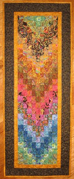 Made from a myriad of over 26 different paisley fabrics, this art quilt wall hanging will look stunning on either your wall or table. I transitioned paisley fabrics so the color flows from one print to the next covering the full color spectrum. This piece was not easy to piece together!  Paisleys have a rich color and pattern to them, and it is not easy to find so many different paisley fabrics! I used a black gray fabric with gold swirls for the larger outside border and a gold fabric for…