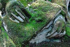 Spectral hands overgrown with moss in Montparnasse Cemetery.