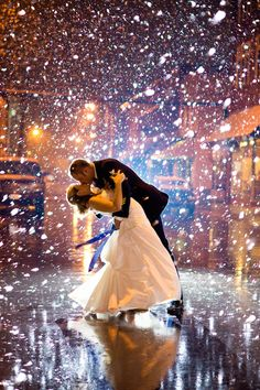 A bride and groom share a kiss in the rain. Photo by Still Frames Photography