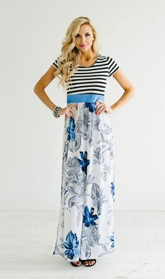 This maxi dress features a black and white stripe bodice, a blue waist band and is followed by a flowy white maxi skirt with a blue and gray floral print.