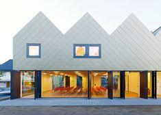 Community hall by Netzwerkarchitekten has a zigzagging golden roof