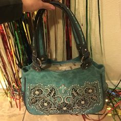 Shop Women's montana west Blue Black size OS Shoulder Bags at a discounted price at Poshmark. Description: New never used suede leather turquoise purse with matching wallet. Three sections inside with silver studs and black floral decor 😍. Sold by oxoxeli. Fast delivery, full service customer support.