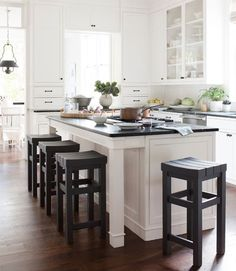 Great mix: Dark-walnut floors, green soapstone counters, black stools, and white cabinets.