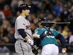 Minnesota Twins' Josh Willingham, left, flips his bat after striking out as Seattle Mariners catcher Jesus Montero heads to the dugout in the first inning of a baseball game, Friday, May 4, 2012, in Seattle