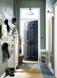 Liten hall med bänk för skor, en spegel, ett skoskåp som rymmer 12 par skor samt krokar för jackor och väskor, allt i svartbrunt.