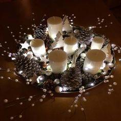 Un plateau lumineux composé de bougies, de pommes de pin, de branches et de petits objets déco pour décorer la table de Noël.