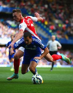 Eden Hazard of Chelsea and Calum Chambers of Arsenal battle for the ball during the Barclays Premier League match between Chelsea and Arsenal at Stamford Bridge on October 4, 2014 in London, England.