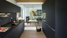 Cocina negra con isla abierta al salón amueblada con el diseño LINE Negro Seda LAH de Santos