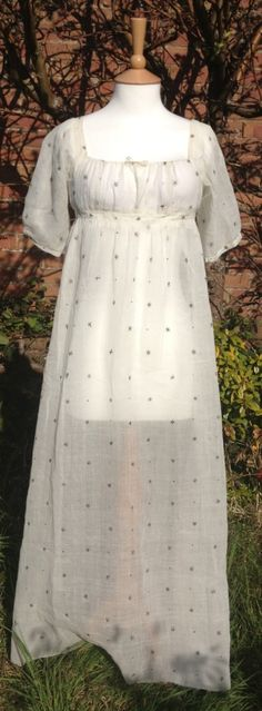 c1805-10 white muslin dress with star and dot design in metallic thread. Back fastening with ties.