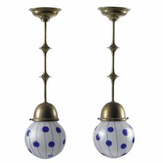 Koloman Moser (1868 - 1918) for Loetz, retailed by Bakalowitz & Söhne brass and glass, the shaped stems each with an opaque spherical shade overlaid with blue lines and dots 51cm. long 1900 - 1905 Sotheby's
