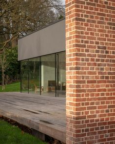 """This brickwork extends out from the edges of the house to hide its other facades, which are wrapped by glass and dark render intended to """"recede visually"""" into the garden."""
