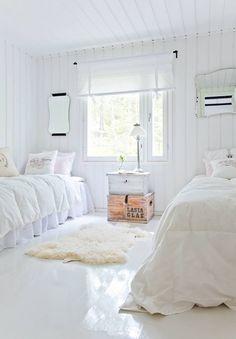 Valkoisin untuvapeittein pedatut sängyt kutsuvat yökyläilemään. Hannele ja Pekka maalasivat vanhat puupaneelit valkoisiksi.