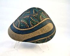 Unique 3 D Art Object, Signed Numbered, Hand Painted Rock, Decorative Art, Radiance Motif, Gold, Silver, Copper on Teal Blue. Home Decor, Office Decor, Gift for Him or Her. A common river rock transformed into a unique 3-d work of art. Teal Blue background has gold, silver, and copper lines radiating out from the center. Ultra Fine Glitter flakes have been added to the metallic paint to catch as much light as possible and give a rich glow to the gold, silver and copper. The design flows all…