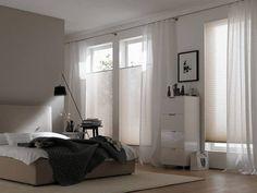 Das Bild zeigt eine dezente Fensterdekoration mit durchsichtigen Vorhängen. Für den nötigen Sonnenschutz sorgen Plissees – ebenfalls in einem natürlichen, hellen Farbton.