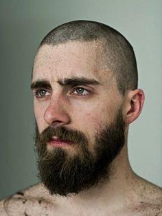 Buzzed hair, full beard, and green eyes.