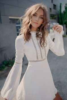 The Willow Bell Sleeve Dress by For Love and Lemons features mock neckline with lace contrast, tiny ladder cutouts on the bodice, long bell sleeves, and floral trim.