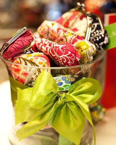 Signatures Invitations  in Glendale Arizona displays Vera Bradley cosmetic bags in a vase with big  green bow.
