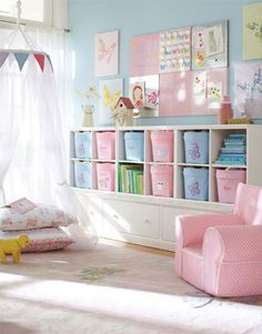 Why This Room Works Soft pink and the palest blue create a delicate contrast in this whimsical playroom. An airy canopy hung from the ceiling forms a sort of room within the room – perfect for hosting tea parties or getting comfy with a favorite book. Open cubbies alternate with personalized canvas bins to make it easy to sort and store books, toys and other collections, and a fabric-covered pinboard above is the perfect place to display artistic creations.