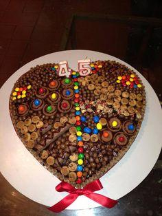 torta brownies rellenaq con crema de chocolate y avellanascon la decoracion de piruli, dandis galletas, chocolates, etc...