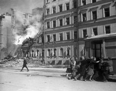 Siege of Leningrad, Oct 1942: As German artillery wrecks yet another building in the center of the city, passengers put their shoulder to the wheel in an effort to save a tram car from a follow-up round. Long range artillery caused thousands of casualties and significant damage during the nearly three years of the city's siege.