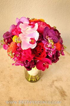 Vibrant Bridal Bouquet of purple Vanda orchids, purple phaleanopsis orchids, white/purple phaleanopsis orchids, yellow craspedia balls, orange Sunset garden roses, red Darcey garden roses, fuchsia stock, purple tulips and fuchsia peonies!! One of our ALL time favorite bouquets