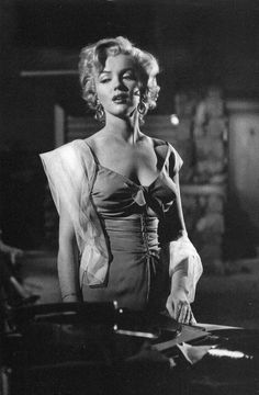 """Marilyn Monroe in a B&W photo taken of her in """"Niagara"""" 1953 at a party by a record player just before she has a very emotional moment in the film."""