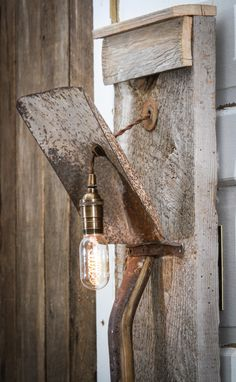 wall lamp made out of old shovel and barn wood