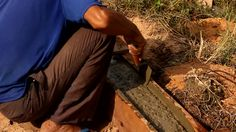 Pouring mixed cement into wooden box to construct fence beam, fence construction site, Laos
