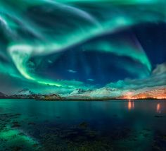 https://flic.kr/p/REZPWa | Rock 'n Roll Aurora | We were already on the way back from an one of the Northern Lofoten beaches with not much luck during the night yet... and suddenly the Aurora lit up like crazy over Torsfjorden! One of the wildest displays I have ever witnessed. Check the EXIF data: 15 seconds at ISO 500! It was so bright, we didn't need high ISOs. I even dared to try a vertical panorama since I not only wanted the sky and the mountains but also the reflections in the water…
