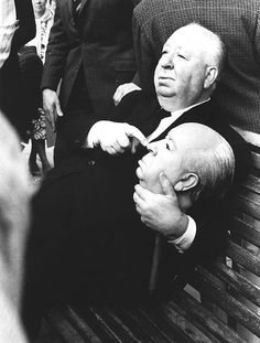 Alfred Hitchcock holding a replica dummy head. The dummy head was used in the 1972 film, Frenzy trailer for the body of Hitchcock floating down the River Thames.