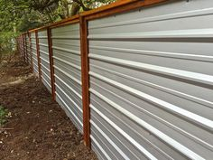 A galvanized corrugated metal fence creates a clean, modern edge to the landscape. Design/Build by LandArc Landscaping & Design