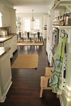 I love EVERYTHING about this kitchen! Down to the hooks for the aprons. The shelves with the matching jars. The floors. The rugs. The metal chairs. All of it!