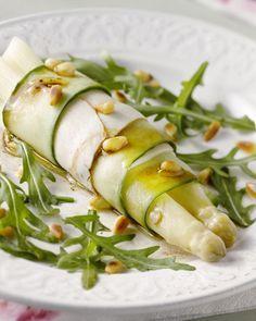 Een lekker makkelijke lunch van asperges, gewikkeld in kippenwit en komkommerslierten. Heerlijk met een notenvinaigrette en afgewerkt met pijnboombitjes.