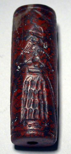 """Cylinder seal: god with flowing vase (MUL GU LA """"The Great One""""?); griffin demon Period: Middle Assyrian Date: ca. 12th century B.C. Geography: Mesopotamia Culture: Assyrian Medium: Jasper, marble Dimensions: 1.83 in. (4.65 cm) Met Museum Accession Number: 41.160.217"""