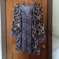 Baby blue animal print blouse Copper colored buttons half way down front. Elastic 3/4 length sleeves. A little sparkle on the front but not too much. Beautiful blouse for dress up or with jeans. Worn once Dress Barn Tops Blouses